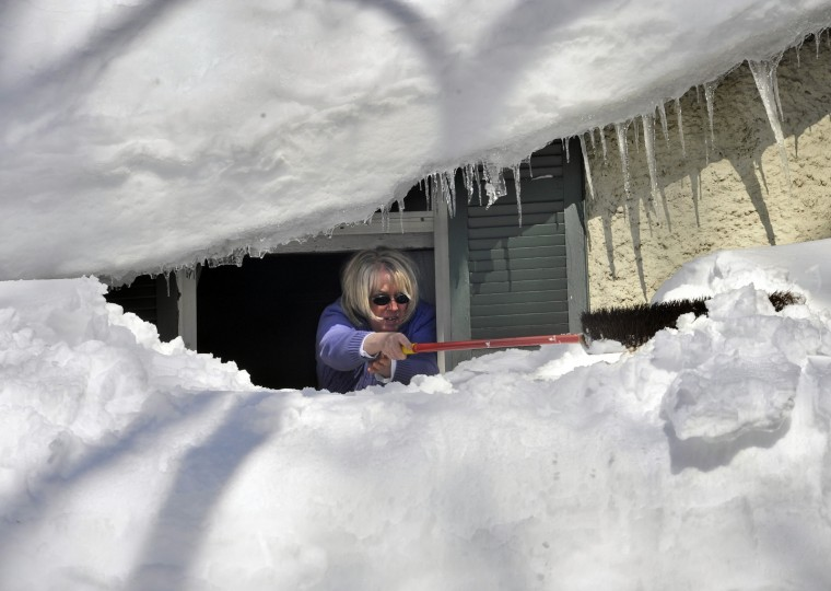 2010: Rebecca Girvin leans out the second floor window of her home in the Lake-Walker neighborhood to push snow off her front porch roof. (Amy Davis/Baltimore Sun)