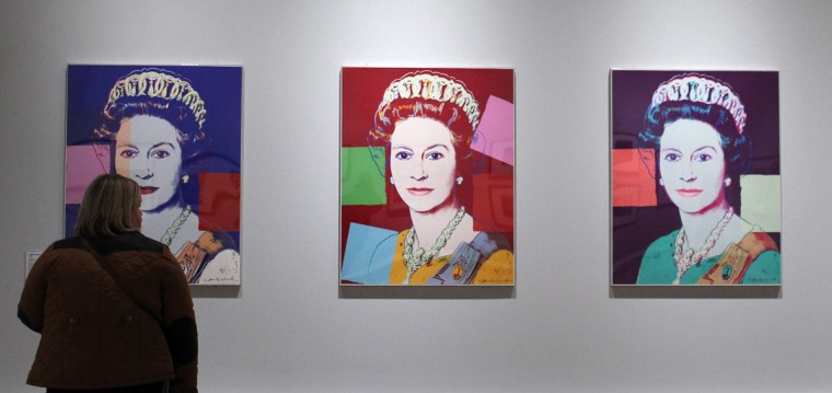 """A women views silkscreen prints of Queen Elizabeth II by artist Andy Warhol during """"The Queen: Art and Image"""" exhibiton at the Ulster Museum in Belfast, Northern Ireland on January 14, 2012. (PETER MUHLY/AFP/Getty Images)"""