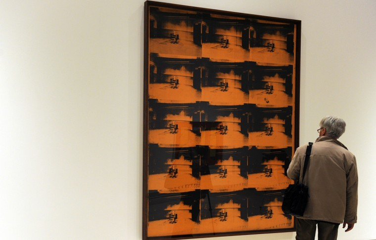 """Visitors look at """"Orange disaster"""" by US artist Andy Warhol belonging to the Guggenheim foundation, as part as an exhibition called """"Guggenheim Collection: The American Avant-Garde 1945-1980"""" on February 6, 2012 at the Palazzo delle Esposizioni in Rome. (GABRIEL BOUYS/AFP/Getty Images)"""