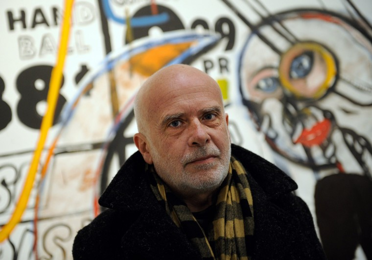 """US-Italian artist Francesco Clemente poses in front of the work """"Handball"""" (1985) by US artist Andy Warhol at the exhibition """"Ménage à trois - Warhol, Basquiat, Clemente"""" during a preview on February 9, 2012 at the Kunst- und Ausstellungshalle der Bundesrepublik Deutschland. (HENNING KAISER/AFP/Getty Images)"""