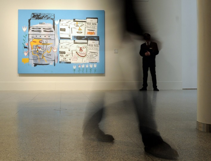 """Visitors walk past the painting """"Stoves"""" (1985) by US artists Andy Warhol and Jean-Michel Basquiat at the exhibition """"Ménage à trois - Warhol, Basquiat, Clemente"""" during a preview on February 9, 2012 at the Kunst- und Ausstellungshalle der Bundesrepublik Deutschland (Art and Exhibition Hall of the Federal Republic of Germany) in Bonn, western Germany. (HENNING KAISER/AFP/Getty Images)"""