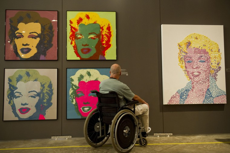 """A visitor takes a picture of paintings from Andy Warhol's series """"Marilyn Monroe, 1967"""", during the """"I want to be Marilyn Monroe"""" exhibition, at the Cinemateca Brasileira on March 4, 2012, in Sao Paulo, Brazil.(NELSON ALMEIDA/AFP/Getty Images)"""