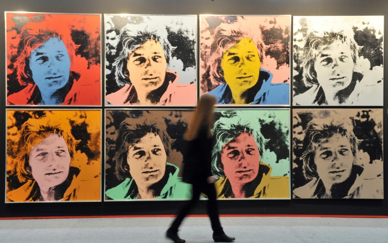 """A woman passes by the artwork """"Gunter Sachs"""" (1972) by artist Andy Warhol at the art fair """"art Karlsruhe"""" in Karlsruhe, western Germany, on March 7, 2012. The fair opens its doors from March 8 to 11, 2012. (ULI DECK/AFP/Getty Images)"""