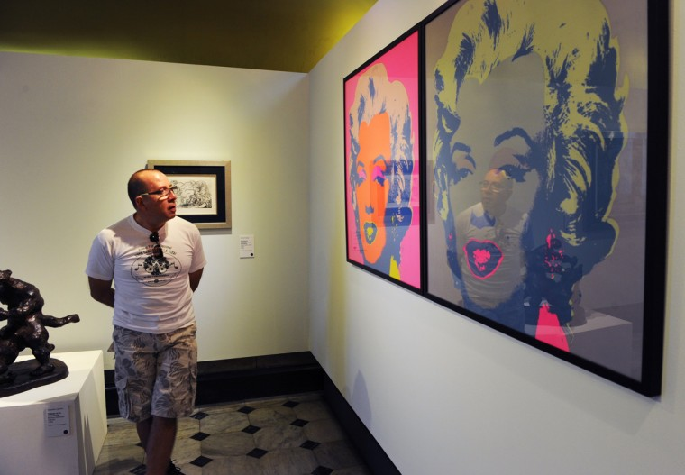 """A visitor stands beside Andy Warhol's """"Marilyn"""" at the National Gallery in San Jose on March 7, 2012. The exhibition is part of the """"Museums and Galleries Route"""" during the XIII International Arts Festival to be held in San Jose from March 1 to 25, 2012. (RODRIGO ARANGUA/AFP/Getty Image)"""