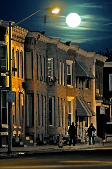 2005: Pedestrians walk along an eerily peaceful E. Lafayette Ave beneath a full moon Monday, Oct. 17, 2005. While many streets in town have plenty of cars, most neighborhoods in this section of town rarely have any parking problem, since many of the homes are vacant and members the community usually can't even afford the costs of having a vehicle. (Karl Merton Ferron/Baltimore Sun)