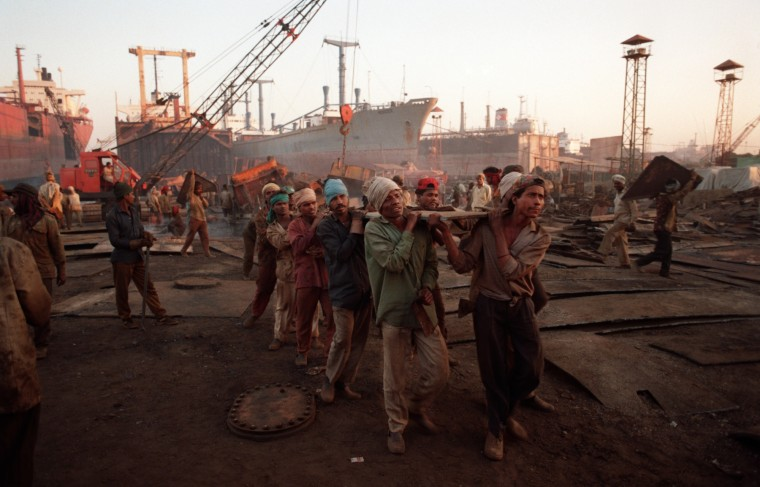 1997: Workers carry a 350kg. sheet of steel across the Annapurna Shipyard in Alang. This technique is the cause of many foot and leg injuries. (Perry Thorsvik/Baltimore Sun)