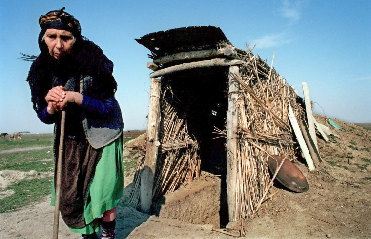 2001: Minavar Sariyeva, 80, is pictured outside the underground dut-out where she lives with her daughter, Suraya Sariyave, 31, in a space barely larger than a walk-in closet, with a ceiling so low one has to stoop. This area is known as Lachin Winterland. For the past century, it was used by shepherds in the winter who brought their sheep from Lachin, a mountainous area, to this lowland which was much warmer. (Algerina Perna/Baltimore Sun)