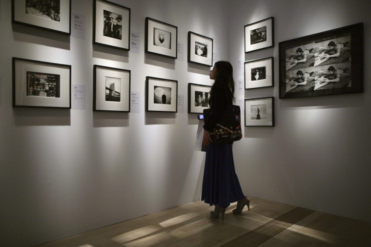 """A woman looks at photographs by Andy Warhol during the media preview of the """"Andy Warhol 15 Minutes Eternal"""" exhibition opening on March 17, 2012 in Singapore. (REUTERS/Tim Chong)"""