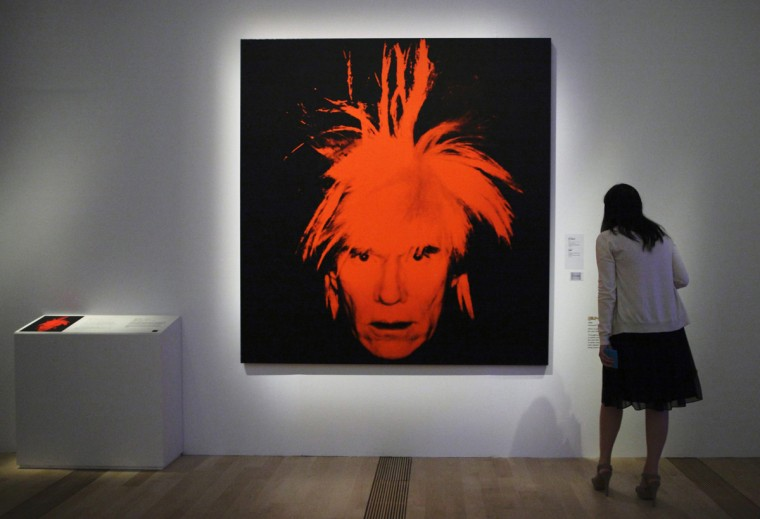 A woman looks at a self portrait by Andy Warhol during the media preview of an exhibition on his works in Singapore March 15, 2012. (REUTERS/Tim Chong)