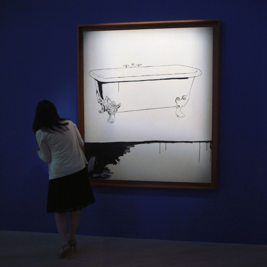 """A woman looks at artwork by Andy Warhol during the media preview of the """"Andy Warhol 15 Minutes Eternal"""" exhibit, which will run from March 17 to August 12, 2012 in Singapore. (REUTERS/Tim Chong)"""