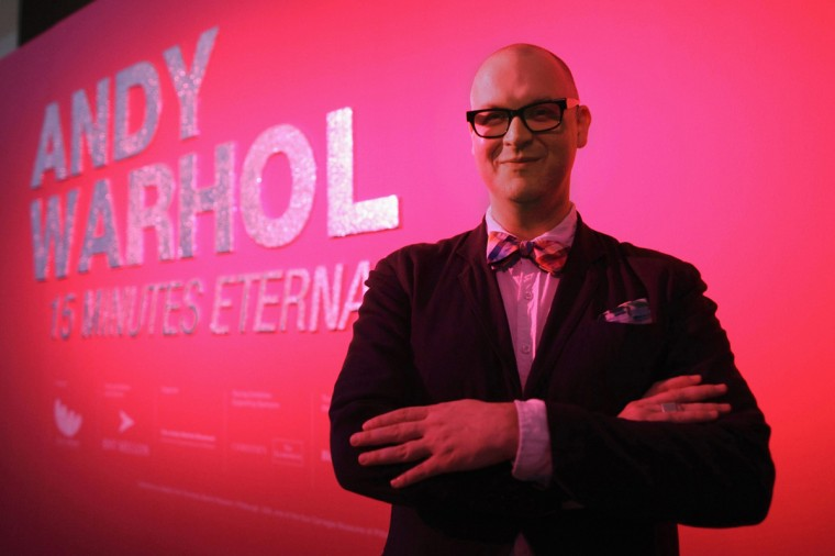 Eric Shiner, the director of the Warhol Museum, poses in front of a sign before the Andy Warhol exhibit at the ArtScience Museum in Singapore March 15, 2012. (REUTERS/Tim Chong )