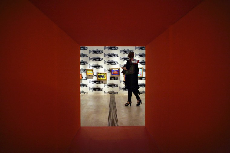 A woman looks at artwork by Andy Warhol during the media preview of an exhibition on his works in Singapore March 15, 2012. (REUTERS/Tim Chong)