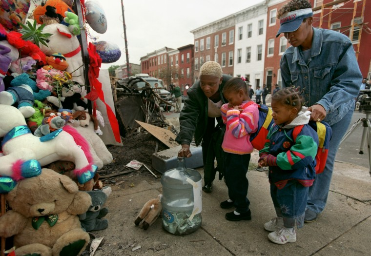 """2002: A city is shaken by the tragic death of the Dawson family. Tinice Copeland, her daughter India Johnson, 4, April Knox and her daughter, Kariah Williams, 2, drop money into a water bottle marked """"The Dawson Family Money."""" (Kim Hairston/Baltimore Sun)"""