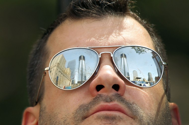 The One World Trade Center building is reflected in the glasses of Bradford Carpentar of Long Island as he looks up at the building. (Spencer Platt/Getty Images)