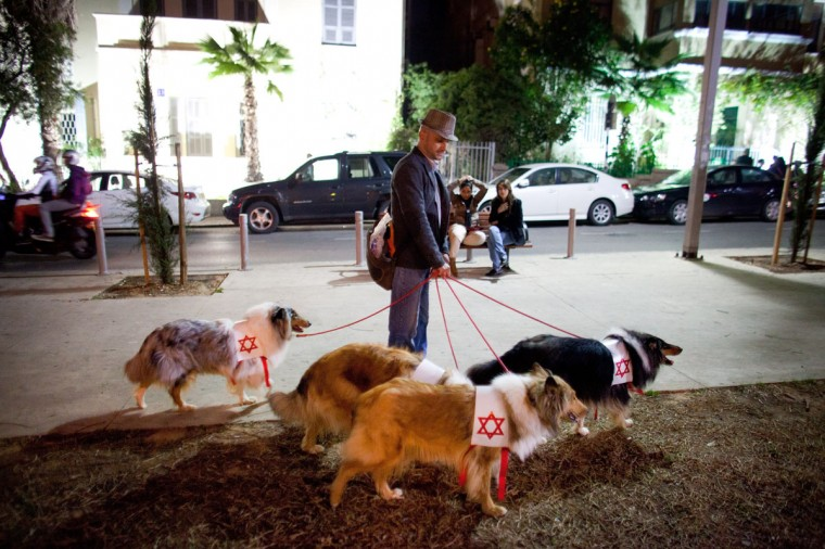 "An Israeli man with dogs takes part in a ""Zombie Walk"" during the Jewish holiday of Purim on March 6, 2012 in Tel Aviv, Israel. The carnival-like Purim holiday is celebrated with parades and costume parties to commemorate the deliverance of the Jewish people from a plot to exterminate them in the ancient Persian empire 2,500 years ago, as described in the Book of Esther. (Uriel Sinai/Getty Images)"