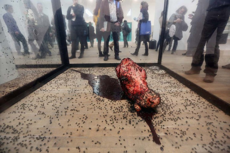 "People view a fly-covered cow's head, part of an artwork by Damien Hirst entitled ""A Thousand Years."" (Oli Scarff/Getty Images)"