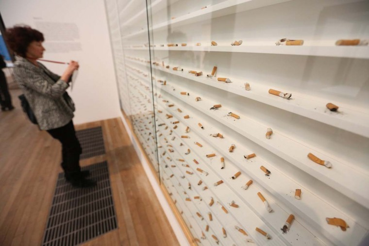 "A woman admires an artwork by Damien Hirst entitled ""Dead Ends Died Out, Examined."" (Oli Scarff/Getty Images)"