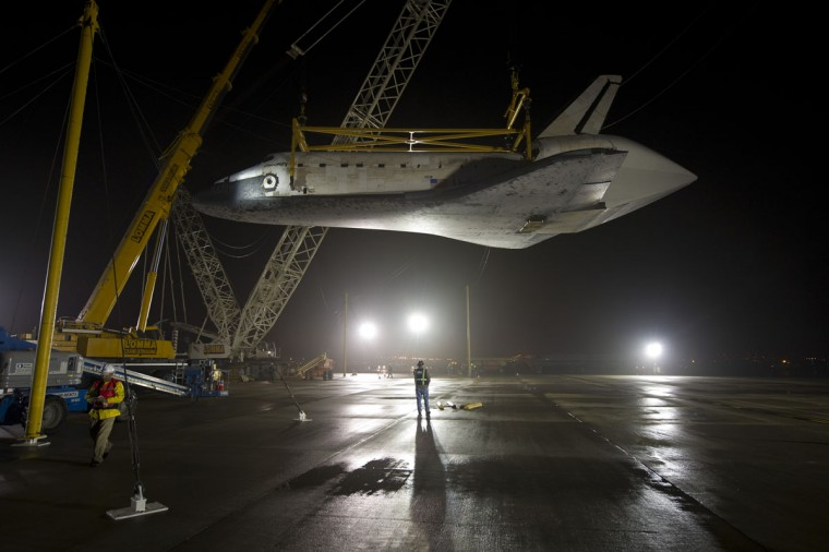 April 19, 2012: Space Shuttle Discovery is suspended from a sling held by two cranes shortly after the NASA 747 Shuttle Carrier Aircraft (SCA) was pushed back from underneath at Washington Dulles International Airport in Sterling, Virginia. (Bill Ingalls/NASA/Getty Images)