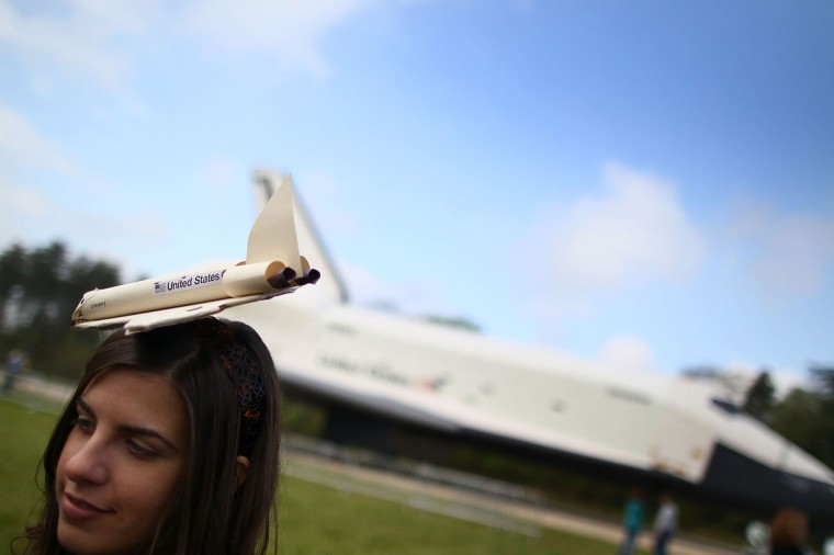 April 19, 2012: Stephanie Harris wears a home made space shuttle hat while standing near the Space Shuttle Enterprise as it sits on a tarmac at the Smithsonian National Air and Space Museum Steven F. Udvar-Hazy Center in Chantilly, Virginia. (Mark Wilson/Getty Images)