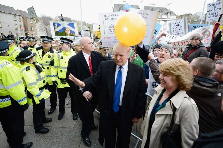 Donald Trump is hit on the head by a member of the public holding a balloon following his address to the Scottish Parliament on April 25. (Photo by Jeff J Mitchell/Getty Images)