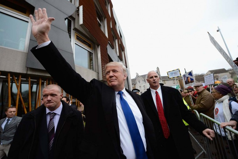 Donald Trump waves to members of the public following his address to the Scottish Parliament on April 25. (Photo by Jeff J Mitchell/Getty Images)