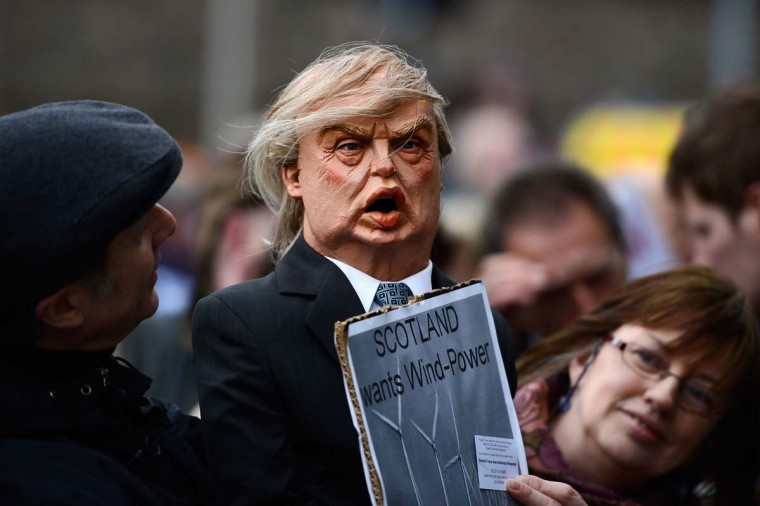 A demonstrator holds a puppet of Donald Trump outside the Scottish Parliament on April 25. Trump spoke of his concerns over a proposed wind farm, mooted to built near his new GBP 1 billion golf resort, telling the Scottish Parliament that they will destroy tourism in the country. (Jeff J Mitchell/Getty Images)