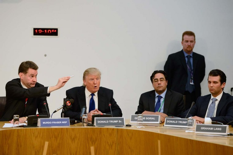 Donald Trump speaks as MSP Murdo Fraser (L) gestures during a press conference following his address to the Scottish Parliament.Trump spoke of his concerns over a proposed wind farm, mooted to built near his new GBP 1 billion golf resort, telling the Scottish Parliament that they will destroy tourism in the country. (Photo by Jeff J Mitchell/Getty Images)