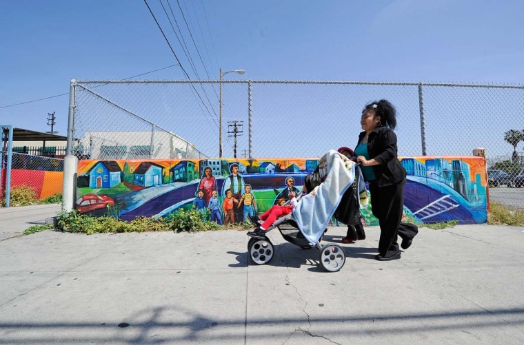 April 28, 2012: A family walks past a mural near Vermont Avenue in South Los Angeles. (Kevork Djansezian/Getty Images)