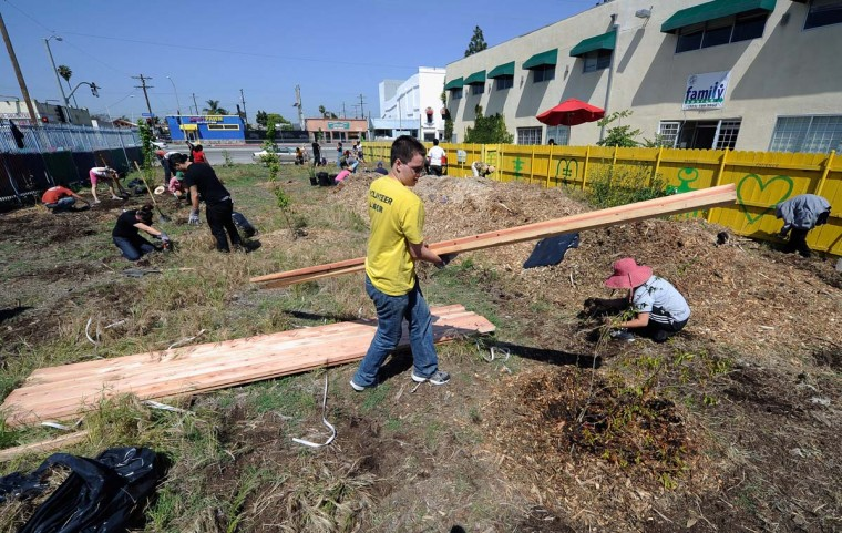 April 28, 2012: Volunteers from LA Works and South Los Angeles nonprofits clean a vacant lot that was the site of a grocery store destroyed during the Los Angeles riots of 1992 on Vermont Avenue. (Kevork Djansezian/Getty Images)