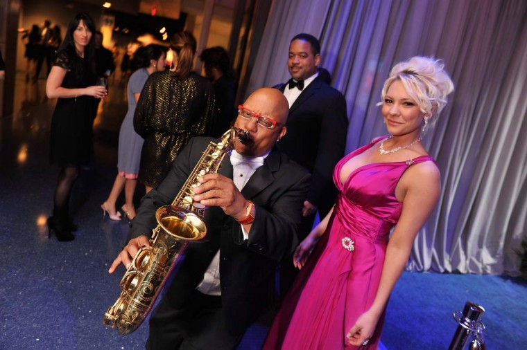 Musician Ski Johnson is seen with a saxophone as Dominique Hatcher looks on as they attend the Capitol File's 7th Annual White House Correspondents' Association Dinner after party at The Newseum on April 28, 2012 in Washington, DC. (Stephen Lovekin/Getty Images)
