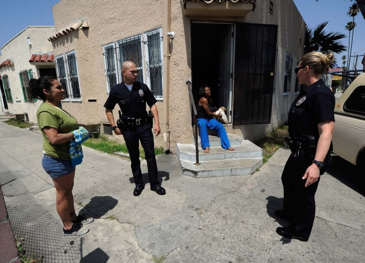 April 29, 2012: Los Angeles Police Department officers from the 77th Street division speak with Tina Kelley (C) after a dispute with her neighbor in South Los Angeles. The 77th Street division patrols the same neighborhood that truck driver Reginald Denny was nearly beaten to death. (Kevork Djansezian/Getty Images)