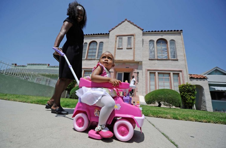 April 29, 2012: A little girl is escorted back home by her mother after a church service in South Los Angeles. (Kevork Djansezian/Getty Images)