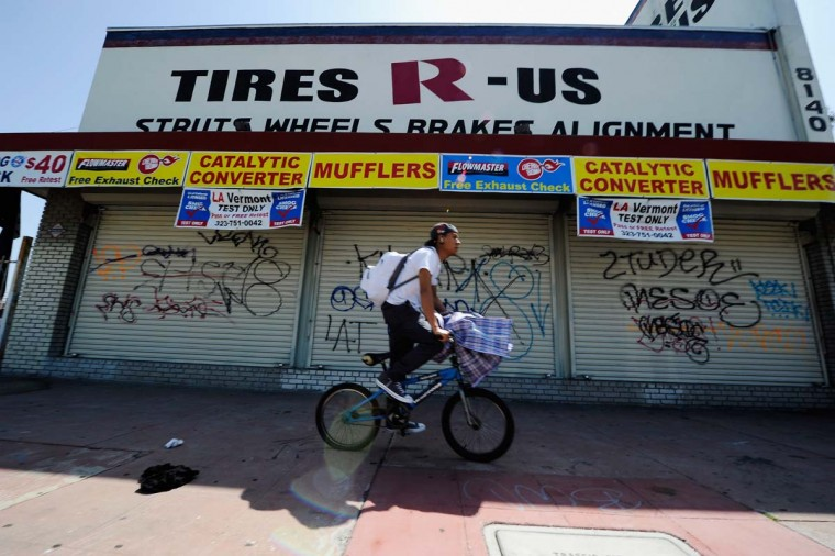 April 29, 2012: A man rides a bike past a store front full of graffiti in South Los Angeles on April 29, 2012 in Los Angeles, California. (Kevork Djansezian/Getty Images)