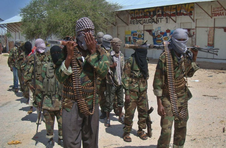 "AL- SHABAAB: Al-Shabaab recruits walk down a street in the Deniile district of Somalian capital, Mogadishu, on March 5, 2012, following their graduation. The walls of the former al-Shabaab base in Baidoa, Somalia, are littered with rudimentary drawings of machine guns and tanks, a note reading ""Fear God, don't write on these walls"" and a sketch of an Al-Qaida flag, homage to the rebel group's international allies. (Mohamed Abdiwahab/AFP/Getty Images)"