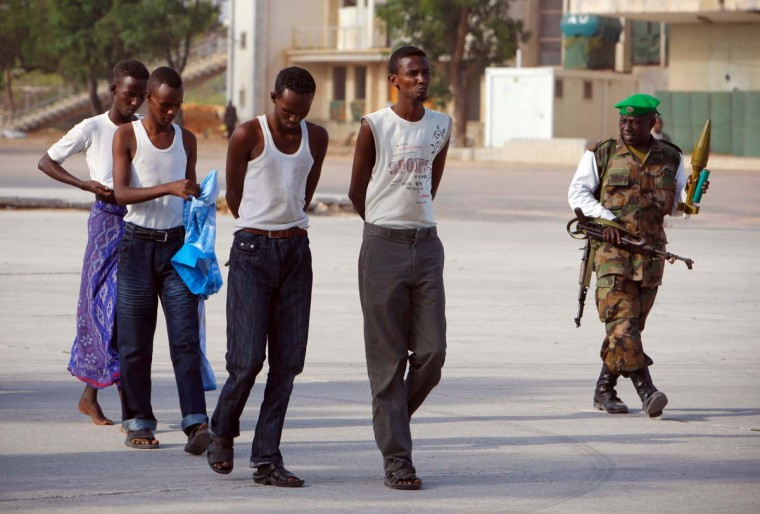 AL- SHABAAB: In this photo taken on March 22, 2012 by the African Union-United Nations Information Support Team, four suspected al-Shabaab insurgents walk on the grounds of the Mogadishu stadium after their capture during a joint security operation conducted by soldiers of the African Union Mission in Somalia (AMISOM) and Somali security services. The four men all in their mid-twenties, were found in possession of a rocket-propelled grenade, two submachine guns and 84 rounds of ammunition, which they had been using to launch attacks against Somali and AU forces. (Stuart Price/AFP/Getty Images)