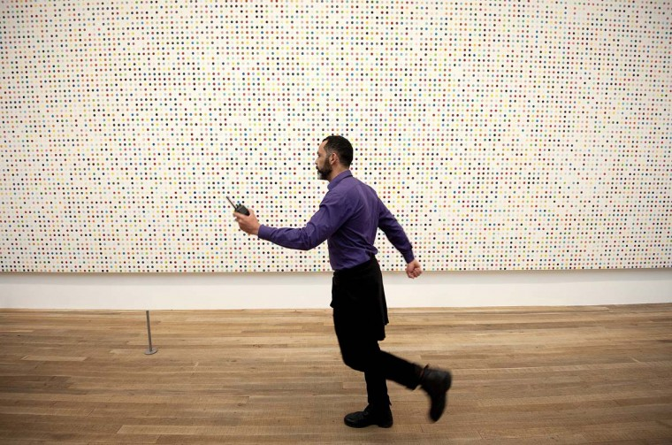 An employee walks past a spot painting by British artist Damien Hirst. (Ben Stansall/AFP/Getty Images)