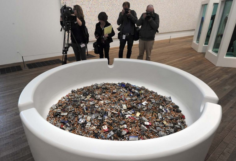 "Photographers take pictures of a work by British artist Damien Hirst entitled ""Crematorium."" (Carl Court/AFP/Getty Images)"