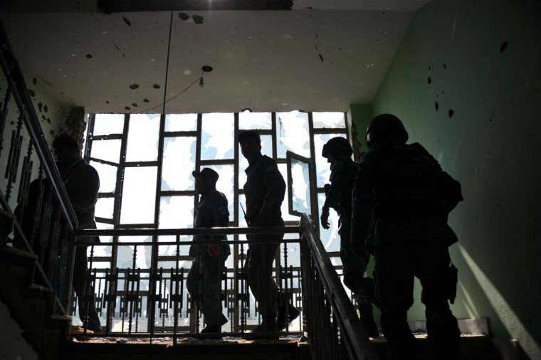 April 16: Police secure a building riddled with bullet holes in Kabul, a day after insurgents used the building to attack the parliament building. (Bay Ismoyo/AFP/Getty Images)