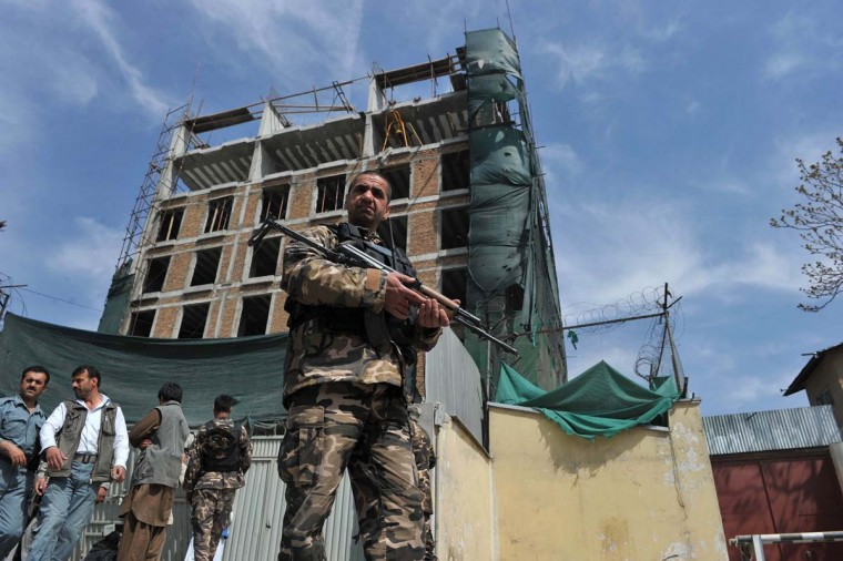 April 16: Afghan policemen stand guard outside the building where Taliban fighters launched an attack in Kabul. (Shah Marai/AFP/Getty Images)
