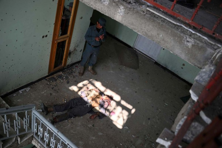 April 16: An Afghan police officer uses a mobile phone to photograph the dead body of an insurgent lying on the floor of a room with bullet riddled walls in Kabul. (Bay Ismoyo/AFP/Getty Images)