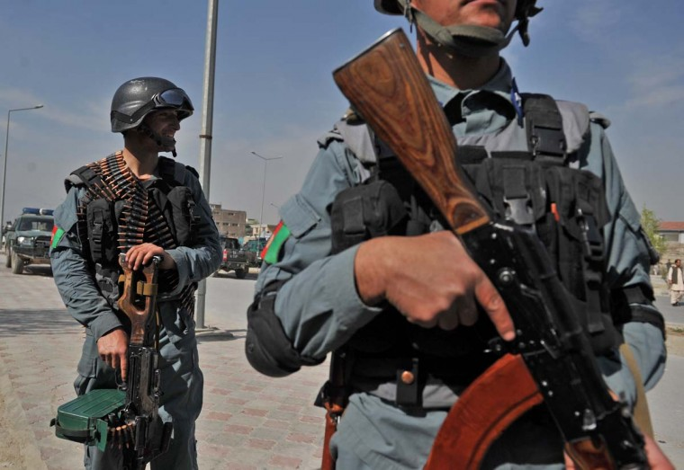 April 16: Afghan policemen stand guard near the building where Taliban fighters launched an attack in Kabul. (Massoud Hossaini/AFP/Getty Images)