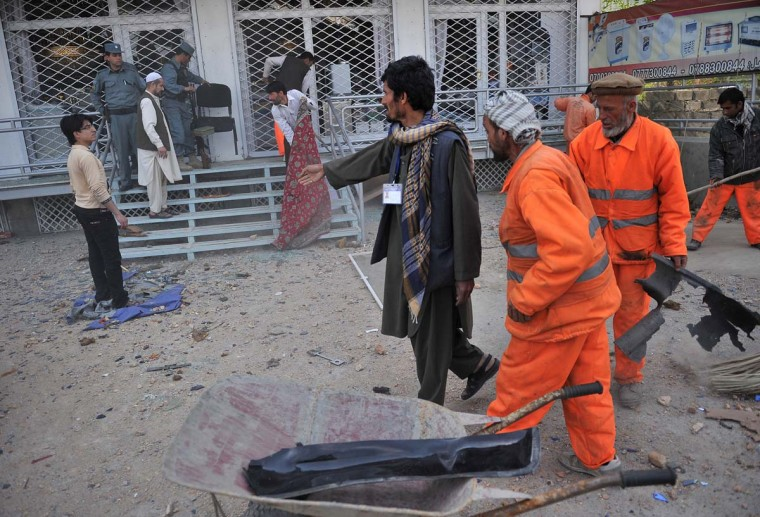 April 16: Municipality workers clean the area outside the building where Taliban fighters launched an attack in Kabul. (Massoud Hossaini/AFP/Getty Images)