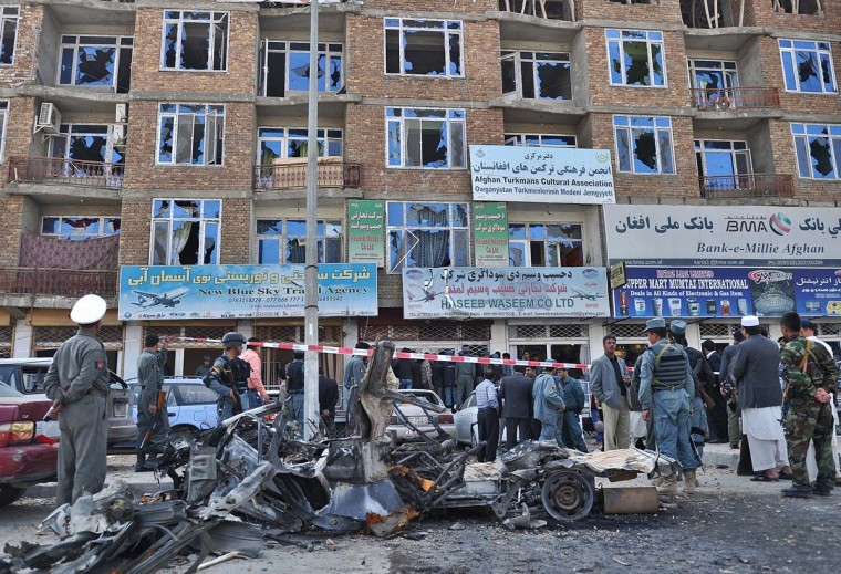 April 16: Afghan policemen and officials stand next to the wreckage of a car used in a suicide attack in front of the building from which insurgents launched an attack, in Kabul on April 16. A total of 47 people were killed and some 65 wounded.(Massoud Hossaini/AFP/Getty Images)
