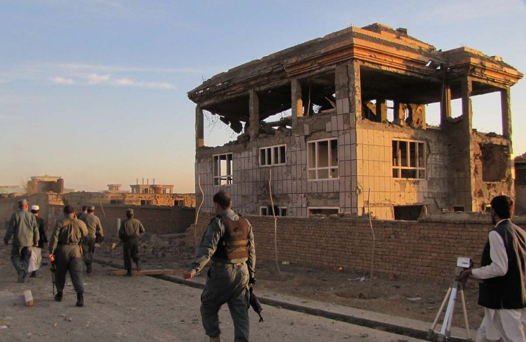 April 16: Afghan policemen walk outside a building from which Taliban fighters launched an attack in Logar province. Afghanistan said its forces regained control of Kabul on April 16, after killing Taliban militants, some disguised as women in burqas, who launched one of the biggest attacks on the capital in a decade of war. (Sabawoon Amarkhil/AFP/Getty Images)