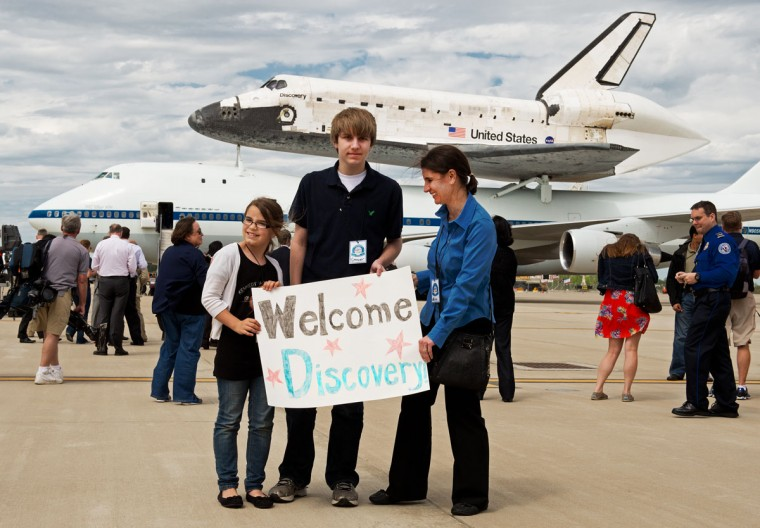April 17, 2012: Guests hold a welcome sign on the tarmac after watching the Space Shuttle Discovery and NASA's Boeing 747 Shuttle Carrier Aircraft (both to rear) land at Washington, Dulles International Airport (Paul J. Richards/AFP/Getty Images)