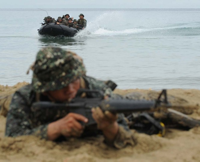 A member of the Philippine marines reconnaissance team (foreground) secures the beach as U.S. and Philippine marines arrive during a beach raid simulation as part of their joint military exercise April 23, 2012 in Puerto Princesa. A senior US commander in the Pacific reaffirmed the United States' mutual defense treaty with the Philippines on April 22, amid increased tensions between the archipelago and China. (Ted Aljibe/AFP/Getty Images)