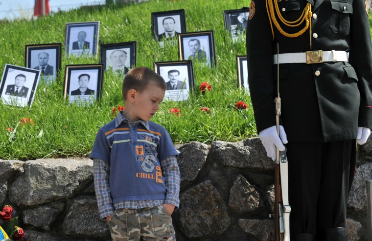 April 26, 2012: A young boy looks at the rifle of a soldier standing guard in front of Chernobyl victims memorial in Kiev during a memorial ceremony. (Genya Savilov/AFP Photo/Getty Images)