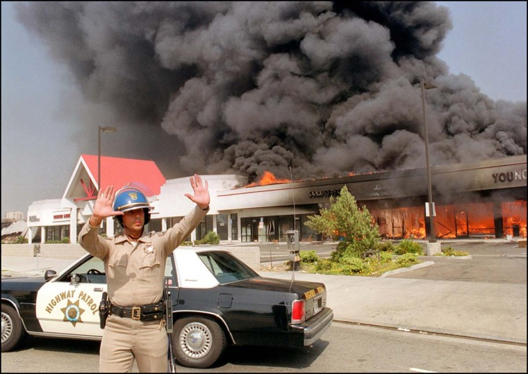 April 30 1992: A California Highway patrolman directs traffic around a shopping center engulfed in flames in Los Angeles. (Carlos Schiebeck/AFP/Getty Images)
