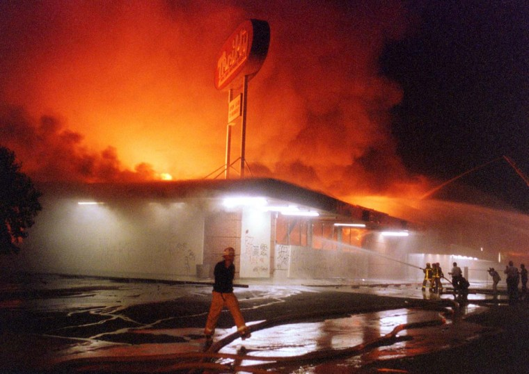 April 29, 1992: Flames roar from a Thrifty Drug store in the Crenshaw area of Los Angeles. (Mike Nelson/AFP/Getty Images)