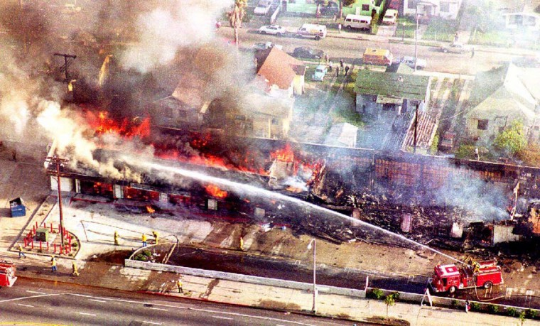 April 30, 1992: A fire department crew sprays water on a burning mini-mall in south Los Angeles after a night of rioting. (Mike Nelson/AFP/Getty Images)